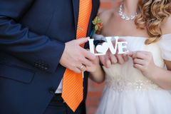 Just married holding plate love. The groom in a black suit and orange tie and the bride in a white dress holding plate love royalty free stock photos