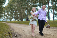 Just married lovers walking in a field in autumn day Stock Photos