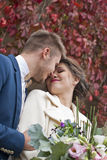 Just married loving couple in wedding dress and suit outdoor in city setting against wall. Happy bride and groom laughing Stock Photo