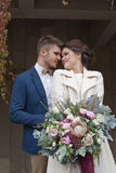 Just married loving couple in wedding dress and suit outdoor in city setting against wall. Happy bride and groom laughing and kiss Stock Images