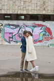 Just married loving hipster couple in wedding dress and suit outdoor in city setting against colorful graffiti wall. Stock Photography
