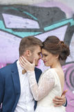 Just married loving hipster couple in wedding dress and suit outdoor in city setting against colorful graffiti wall. Royalty Free Stock Photo