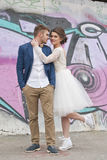 Just married loving hipster couple in wedding dress and suit outdoor in city setting against colorful graffiti wall. Royalty Free Stock Photos