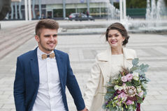 Just married loving hipster couple in wedding dress and suit outdoor in city setting against colorful graffiti wall. Stock Photos