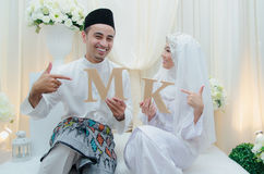 Just married Malay couple. Kuala Lumpur, Malaysia – April 5, 2014. Just married Malay couple showing props and cheerful their solemnization event Royalty Free Stock Photo