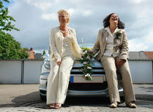 Just married mature lesbian couple. Mature lesbian couple posing in formal dress in front of a car after the official same-sex marriage ceremony Stock Images