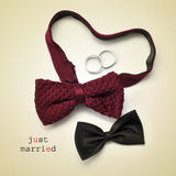 Just married. A pair of bow ties, one of them forming a heart, wedding rings and the sentence just married on a beige background, with a retro effect Royalty Free Stock Photos