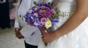 Just Married. Recently married couple awaiting in the church, bride holding his flowers in the ceremony of his wedding, purple, pink and blue flowers in a Royalty Free Stock Photos