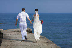 Just married running along pier Royalty Free Stock Photos