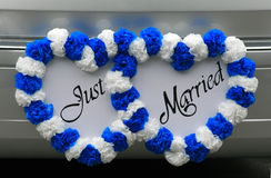 Just Married Sign on Vehicle. These intertwinned Just Married hearts decorate the back of a vehicle Royalty Free Stock Photo