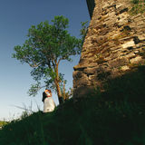 Just married stand behind a stone castle wall Stock Image