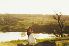 Just married stand calm on the stone behind a lake Royalty Free Stock Photo