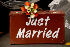 Just married suitcase. Old brown suitcase with just married written on it & brides dress & car in the background Stock Photos