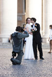 Just married - Wedding shooting photographer. A newly married couple posing in St. Peters Square with a photographer Royalty Free Stock Photos