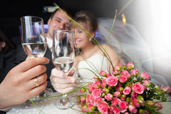 Just married young couple. Inside limo with flowers and champagne Stock Photo
