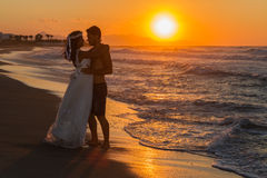 Just married young couple on a hazy beach at dusk Royalty Free Stock Photo