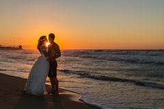 Just married young couple on a hazy beach at dusk Stock Photos