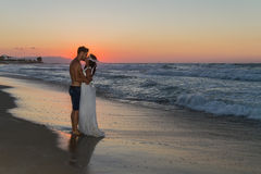 Just married young couple on a hazy beach at dusk Stock Photo