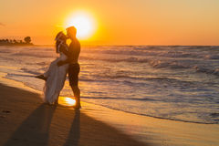 Just married young couple on a hazy beach at dusk Royalty Free Stock Images