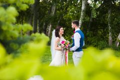 Just marriend young couple in love smiling at nature green background. Groom and bride smile to each other in the forest with pink flower bouquet and beautiful Royalty Free Stock Image