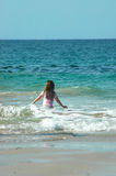 Just me and the sea!. Backview of a caucasian white girl child with long blond hair standing and playing in the water of the Indian ocean on a beach in South Stock Photos