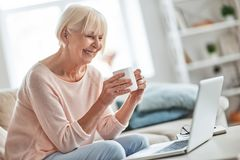 Just a minute to herself. Beautiful senior woman drinking coffee while relaxing on the couch at home royalty free stock images
