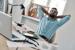 Just a minute to rest. Young modern businessman keeping hands behind head and eyes closed while sitting in the office stock photography
