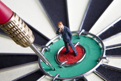 Just missed the target. Businessman figurines placed on a dart board stock images