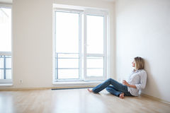Just moved in: beautiful young woman finally sitting down Stock Photography