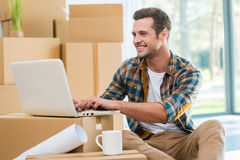 Just moved in. Handsome young man sitting on the floor and working on laptop while cardboard boxes laying in the background Stock Images