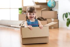 Just moved into a new home. Chid girl sits inside box. Royalty Free Stock Image