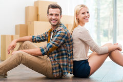 Just moved to their new apartment. Cheerful young couple sitting on the floor of their new apartment while cardboard boxes laying in the background Royalty Free Stock Images