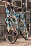 Just an old blue bicycle. An old blue bicycle parked against a guardrail Stock Photography