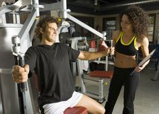 Just one more!. Young couple, working out in gym. Man is sitting and picking up dumbbell. He looks tired. Woman is standing close by man. Smiling and looking at Royalty Free Stock Photos