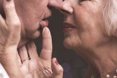 Just one more kiss. Close shot of elder couple close to kiss, when the women is touching man's face and his lip Stock Image