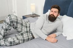 Just one more minute in bed. energy and tiredness. bearded man hipster want to sleep in morning. brutal sleepy man in. Bedroom. mature male with beard in pajama royalty free stock image