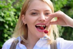 Just one more reason to smile. Pretty woman with happy smile. Happy woman hold cherry berries in healthy teeth. Sensual. Woman with white smile. Beauty look of stock photo