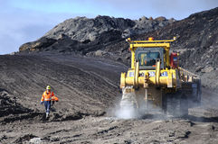 Just passing by. WESTPORT, NEW ZEALAND, AUGUST 31, 2013: Coal mine worker passes a dozer at Stockton Coal Mine, Westland, New Zealand Royalty Free Stock Photo