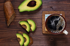 Just prepared quick lunch. Prepared by myself simple lunch with brown baguette styled bread and avocado and coffee on vintage wooden table royalty free stock images