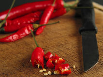 Just put them into your food :-). Close-up of sliced chilli on wood with knife Royalty Free Stock Images