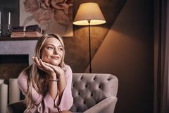 Just a quiet contemplation. Attractive young woman looking away. And smiling while sitting in the armchair royalty free stock photos