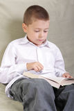 Just reading. Boy in white shirt sitting on sofa and reading Royalty Free Stock Photography