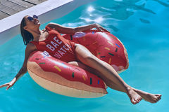 Just relaxing. Attractive young woman in swimwear smiling while floating on the inflatable ring in the swimming pool Stock Photo