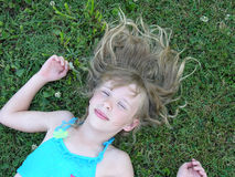 Just resting. A young girl resting on the grass with her hair around her Royalty Free Stock Image