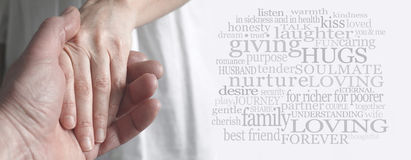 Just before the ring goes on. Wide soft focus cropped image of a man holding a woman's hand tenderly with a love and marriage related word cloud on right hand royalty free stock photo