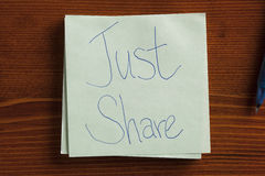 Just Share written on a note Royalty Free Stock Photos