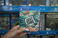 Just Sing. Bratislava, Slovakia, circa april 2017: Man holding Just Sing videogame on Sony Playstation 4 console in store Stock Photos