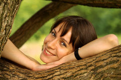 Just smile. Brown-haired young woman smiling friendly on willow branch Royalty Free Stock Photo
