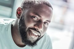 Close up of handsome foreigner that watching you. Just smile. Happy bearded man showing his smile and bowing head while looking straight at camera royalty free stock photos