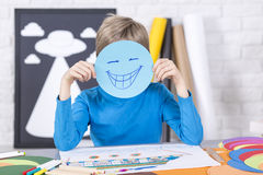 Just smile and have fun. Young funny boy holding piece of papers with smile on his face. Sitting in a studio full of colorful papers stock images